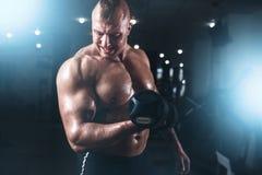 Atleta muscolare che posa con la testa di legno nella palestra di sport Fotografie Stock Libere da Diritti