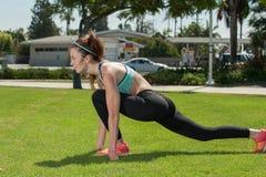 Atleta muscolare che si scalda sull'erba Fotografie Stock
