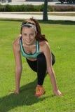 Atleta muscolare che sorride durante l'allungamento Fotografia Stock