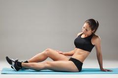 Atleta muscolare della giovane donna che allunga sul gray Immagine Stock Libera da Diritti