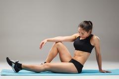 Atleta muscolare della giovane donna che allunga sul gray Fotografia Stock Libera da Diritti
