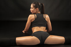 Atleta muscolare della giovane donna che si siede nella spaccatura Fotografie Stock Libere da Diritti