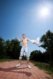 Atleta muscular joven que quita su camisa Fotografía de archivo