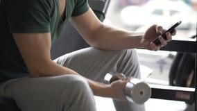 Atleta muscular que hace el ejercicio de la pesa de gimnasia, comprobando rutina del entrenamiento en el artilugio app almacen de metraje de vídeo