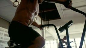 Atleta muscular que hace entrenamiento intenso en la bici del gimnasio almacen de video