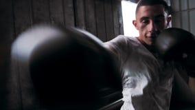 Atleta muscular que se resuelve con el saco de arena en el gimnasio, entrenamiento masculino del boxeador Front View metrajes