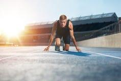 Atleta na posição começar pronta para começar uma raça imagens de stock royalty free