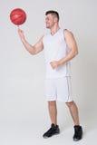 Atleta negli sport uniforme e pallacanestro Fotografie Stock Libere da Diritti