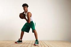 Atleta negro sonriente de los jóvenes que juega a baloncesto Imagen de archivo libre de regalías