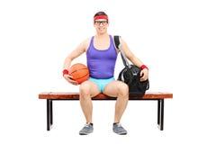 Atleta nerd che giudica una pallacanestro messa su un banco Fotografie Stock