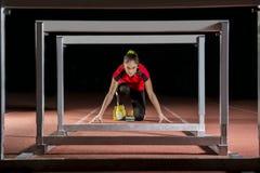 Atleta nos blocos começar com obstáculos imagens de stock