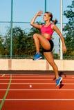 Atleta novo, bonito da menina no sportswear que faz o aquecimento no estádio Foto de Stock Royalty Free