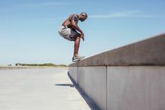 Atleta novo descamisado que faz o exercício de salto Fotos de Stock