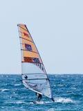 Atleta novo em um fato de esporte da cor que exercita no windsurfe dentro Imagens de Stock