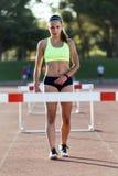 Atleta novo que salta sobre um obstáculo durante o treinamento no trac da raça foto de stock