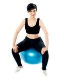 Atleta novo que senta-se em uma esfera suíça Fotos de Stock Royalty Free