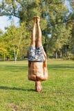 Atleta novo Standing na cabeça no parque Exercício da rua fotos de stock