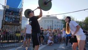 Atleta obezwładniająca z protetycznym nóg podwyżek barem nad głowa obok trenera przy sport rywalizacjami Outdoors zbiory wideo