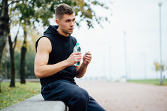 Atleta odpoczywa na ławce w parku po biegać z butelką woda Odpoczywa ciężkiego trening zdjęcie royalty free