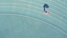 Atleta orgulhoso que faz um regaço de vitória com a bandeira na pista video estoque