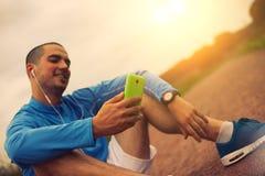 Atleta patrzeje smartphone z zegarem i hełmofonami Zdjęcia Royalty Free