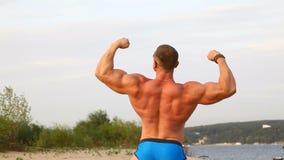 Atleta perfetto di misura nell'ente muscolare di manifestazione del costume da bagno video d archivio
