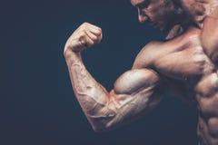 Atleta pokazuje jego pięknego ciało na czarnym tle Zdjęcie Stock