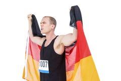 Atleta pozuje z niemiec flaga po zwycięstwa obrazy royalty free