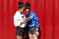 Atleta przyjaciele patrzeje telefon komórkowego Zdjęcia Royalty Free