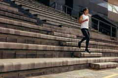 Atleta que corre abajo de las escaleras de un soporte del estadio Foto de archivo
