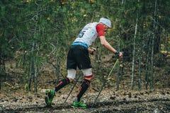Atleta que corre con los polos que caminan del nordic en calcetines de la compresión Fotos de archivo libres de regalías