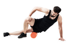 Atleta que da masajes y que estira al músculo iliotibial de la banda con el rodillo de la espuma imagenes de archivo