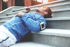 Atleta que descansa nas escadas após movimentar-se, encontrando-se na rua, na fita com telefone e nos fones de ouvido com música  imagens de stock royalty free