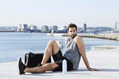 Atleta que descansa pelo mar imagens de stock