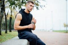 Atleta que descansa sobre banco en parque después de correr con la botella de agua Descanse un entrenamiento duro Imagen de archivo