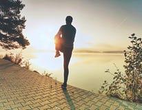 Atleta que estira los músculos de la parte inferior del cuerpo antes de correr que va foto de archivo libre de regalías
