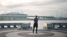 Atleta que estira su brazo en la ropa de deportes para el desafío de funcionamiento almacen de metraje de vídeo