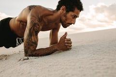 Atleta que faz o exercício do núcleo no dun da areia imagem de stock