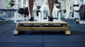 Atleta que hace ejercicios del salto con el tablero del paso en un gimnasio almacen de metraje de vídeo