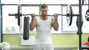 Atleta que hace el ejercicio para el bíceps con el barbell Trenes musculares jovenes del hombre en el gimnasio Entrenamiento de C imagen de archivo libre de regalías