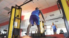 Atleta que hace flyes del cable en la máquina de la cruce para los músculos del pecho y del hombro almacen de video