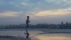 Atleta que hace los ejercicios físicos que corren, reflexión de la mañana en el charco, ciudad almacen de metraje de vídeo