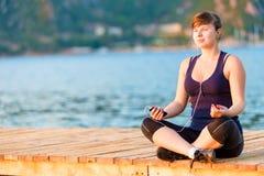 Atleta que hace yoga en el embarcadero Fotos de archivo libres de regalías