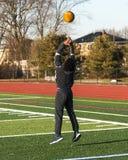 Atleta que lanza gastos indirectos de la bola de medicina al revés Fotografía de archivo libre de regalías