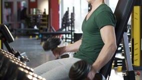 Atleta que levanta las pesas de gimnasia alternativamente pesadas en músculos crecientes del gimnasio, levantamiento de pesas almacen de video