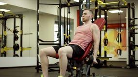 Atleta que levanta os pesos e que trabalha seu bíceps no gym filme