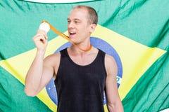 Atleta que muestra su medalla de oro delante de la bandera brasileña Fotografía de archivo libre de regalías