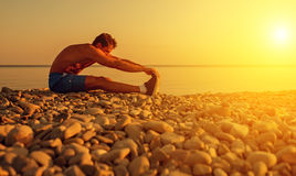 Atleta que practica, yoga en la playa en la puesta del sol Imágenes de archivo libres de regalías