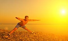 Atleta que pratica, ioga na praia em sóis fotos de stock
