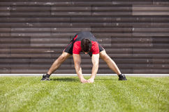 Atleta que se calienta y que estira foto de archivo